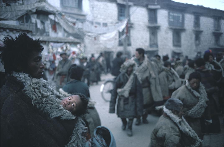 1981年,西藏自治区拉萨市,大街上一位父亲用厚羊毛大衣裹着自己的孩子