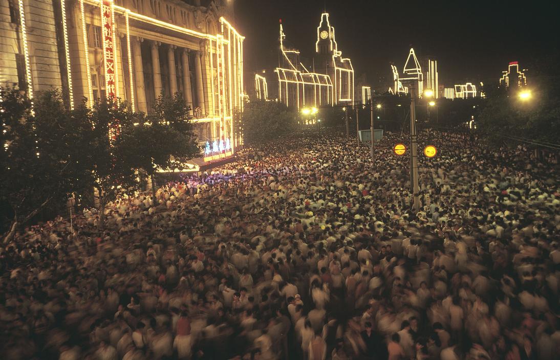 1983年,中国上海市,夜晚灯光下拥挤的人们