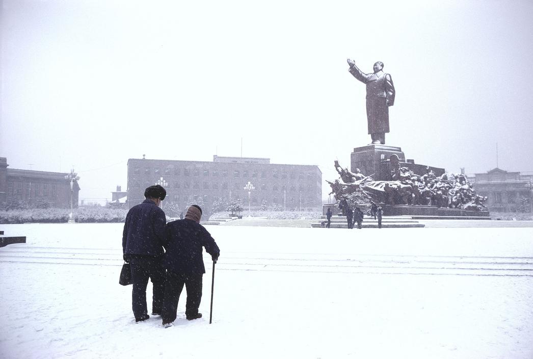 1984年,辽宁省沈阳市,一位母亲同她的儿子经过毛主席雕塑前