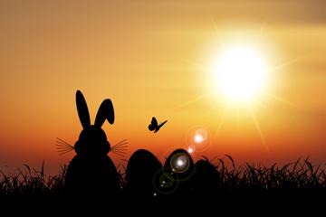 夕阳下的兔子和彩蛋剪影矢量图